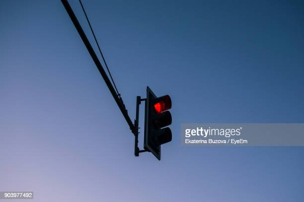 Low Angle View Of Illuminated Stoplight Against Clear Blue Sky