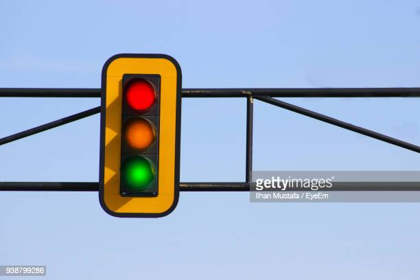 low angle view of illuminated stoplight against clear blue sky - stoplight stock pictures, royalty-free photos & images