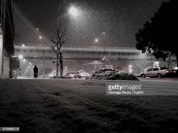 Low Angle View Of Illuminated Street At Night While Snowing