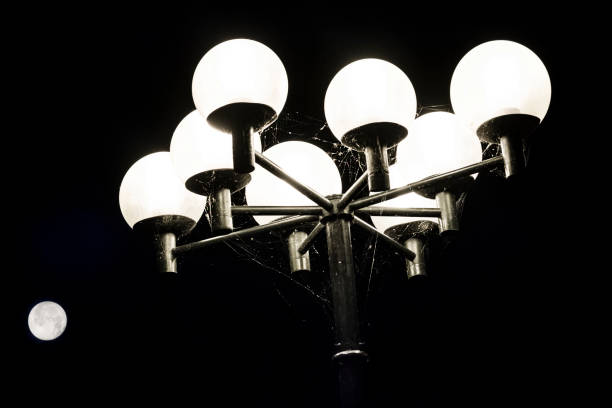 Low Angle View Of Illuminated Street Light Against Black Background