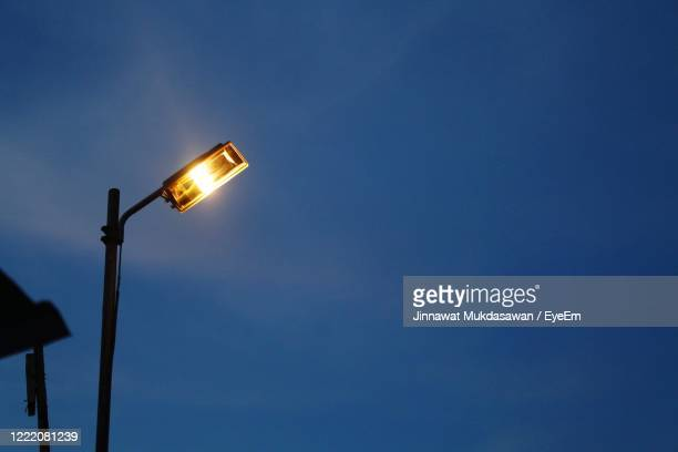 low angle view of illuminated street light against blue sky - international team soccer stock pictures, royalty-free photos & images