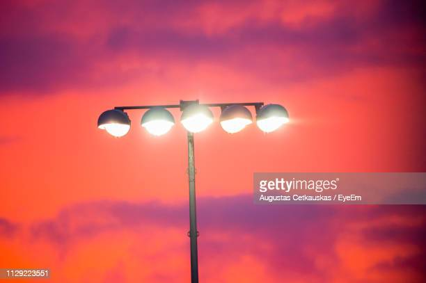 low angle view of illuminated street light against orange sky - cetkauskas stock pictures, royalty-free photos & images