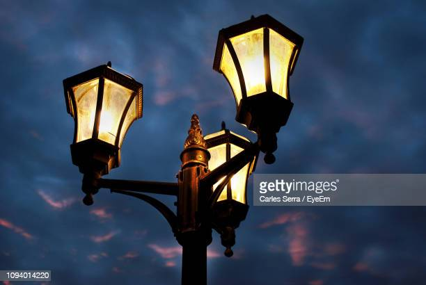 low angle view of illuminated street light against sky - ガス燈 ストックフォトと画像