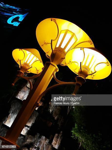 low angle view of illuminated street light at night - muro stock photos and pictures
