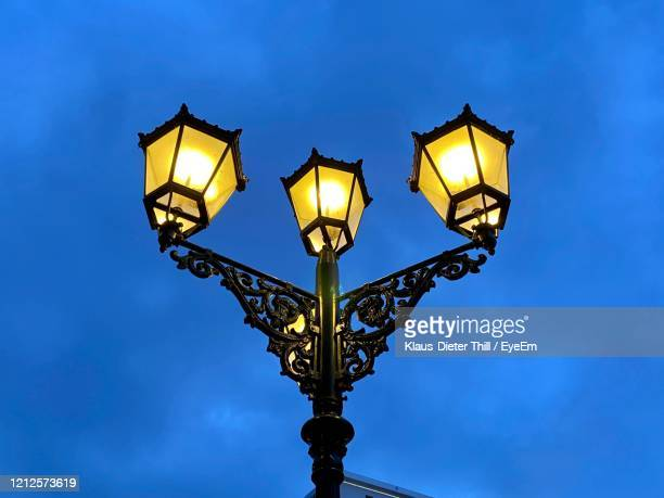 low angle view of illuminated street light - klaus-dieter thill stock-fotos und bilder