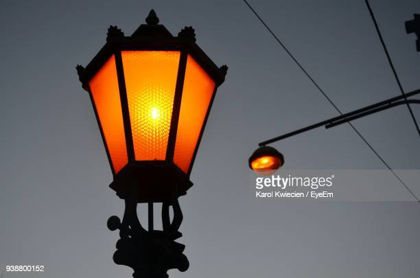 low angle view of illuminated street lights against clear sky - ガス燈 ストックフォトと画像