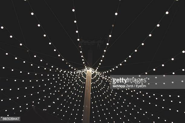 Low Angle View Of Illuminated String Lights Against Clear Sky At Night