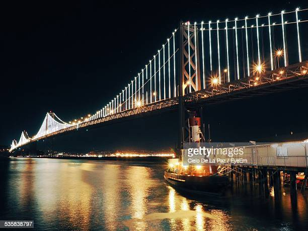 low angle view of illuminated suspension bridge over sea against clear sky at night - cielo stock pictures, royalty-free photos & images