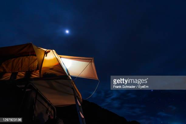 low angle view of illuminated tent against sky at night - frank schrader stock pictures, royalty-free photos & images
