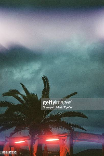 Low Angle View Of Illuminated Tent At Beach Against Cloudy Sky At Dusk