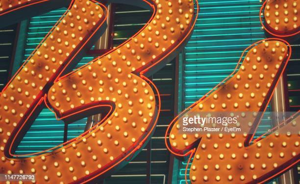 low angle view of illuminated text on building in city - las vegas stock-fotos und bilder