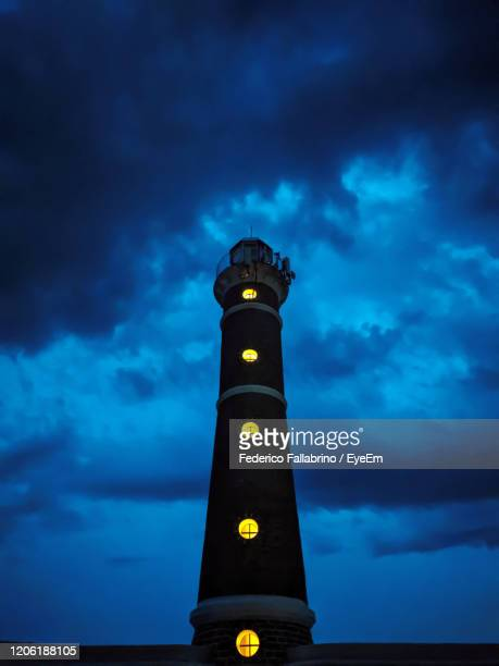 low angle view of illuminated tower against sky at dusk - jose ignacio lighthouse stock pictures, royalty-free photos & images