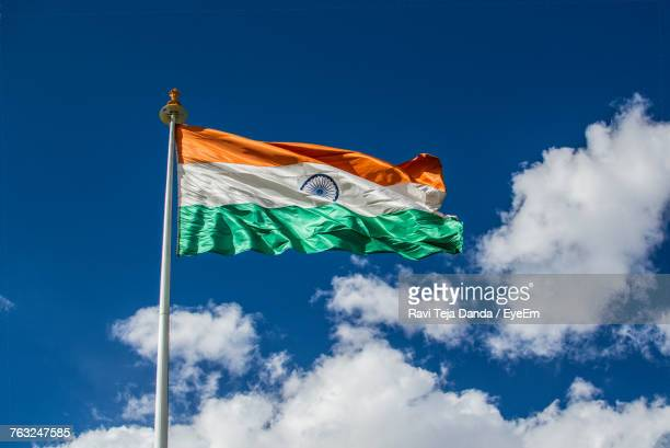 low angle view of indian flag against blue sky during sunny day - indian flag stock pictures, royalty-free photos & images