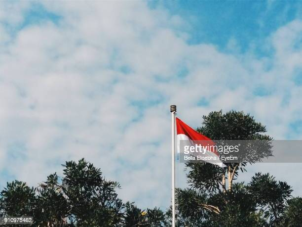 low angle view of indonesian flag against sky - indonesia flag stock photos and pictures