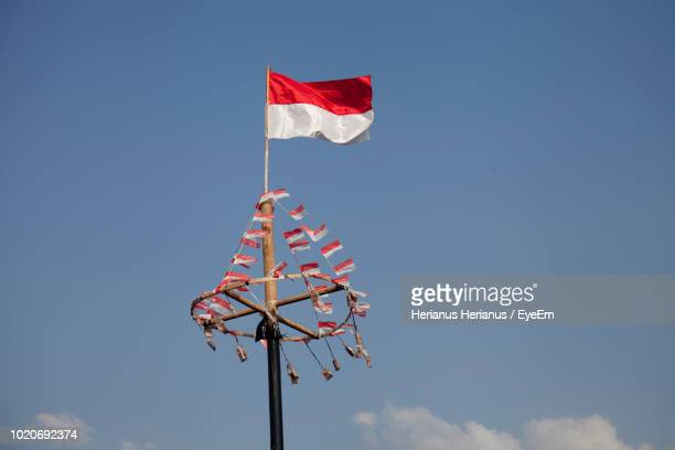 low angle view of indonesian flag waving against sky - indonesia flag stock photos and pictures