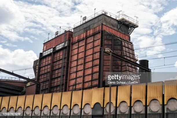 low angle view of industrial building against sky - charleroi stock pictures, royalty-free photos & images