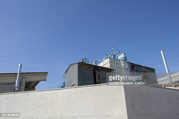 Low angle view of industrial building against sky