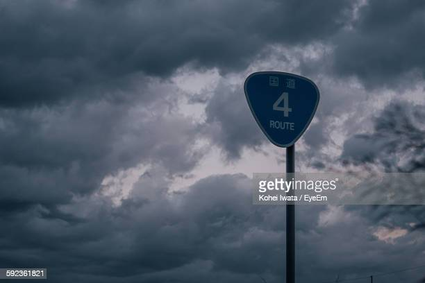 Low Angle View Of Information Sign Against Cloudy Sky