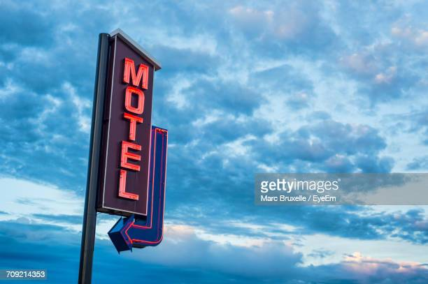 low angle view of information sign against sky - motel stock photos and pictures