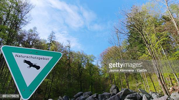 Low Angle View Of Information Sign And Trees Against Sky At Forest