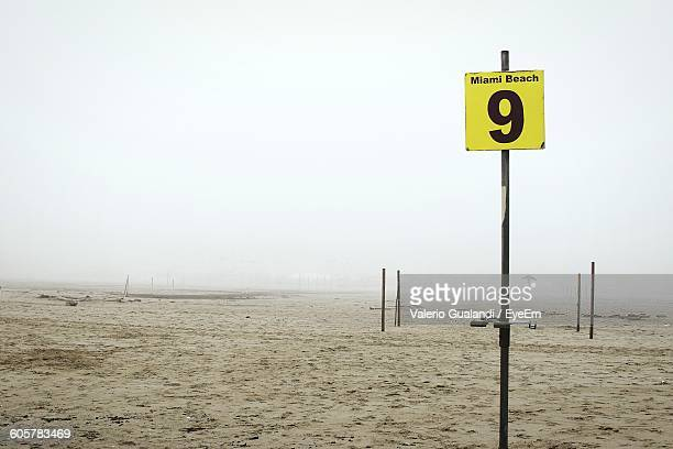 Low Angle View Of Information Sign On Sandy Field Against Clear Sky During Foggy Weather