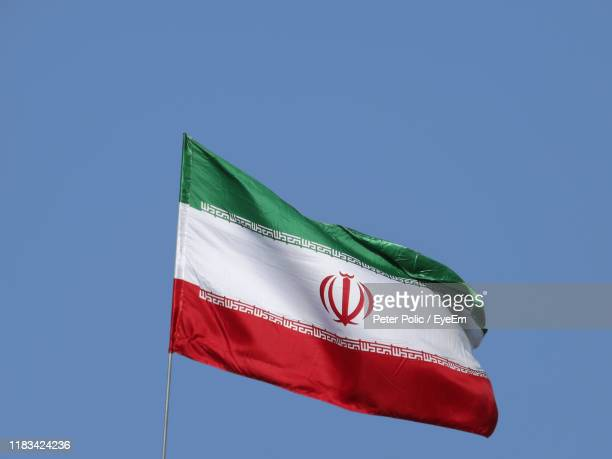 low angle view of iranian flag against clear blue sky - iran flag stock photos and pictures