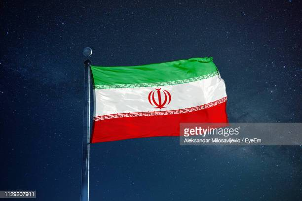 low angle view of iranian flag against star field sky - iran flag stock photos and pictures