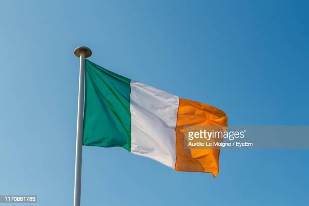 low angle view of irish flag against clear sky - irish flag stock pictures, royalty-free photos & images