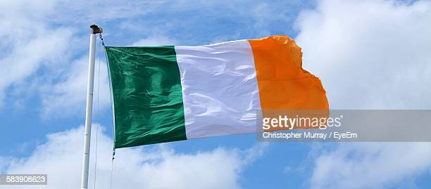 low angle view of irish flag against sky - irish flag stock pictures, royalty-free photos & images