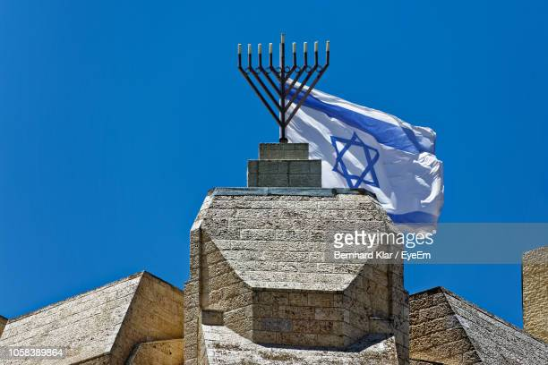 low angle view of israeli flag waving on historic building against clear blue sky - israel independence day stock pictures, royalty-free photos & images