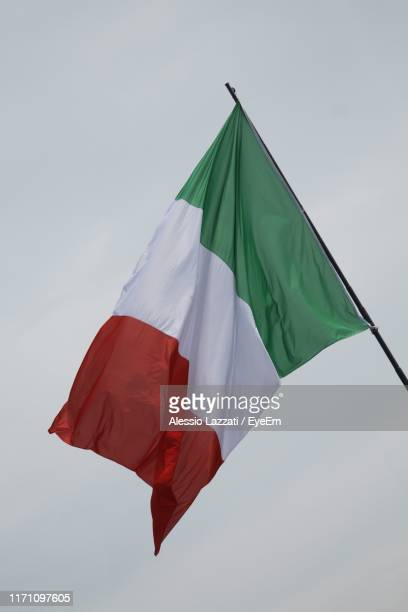 low angle view of italian flags against clear sky - tricolore foto e immagini stock