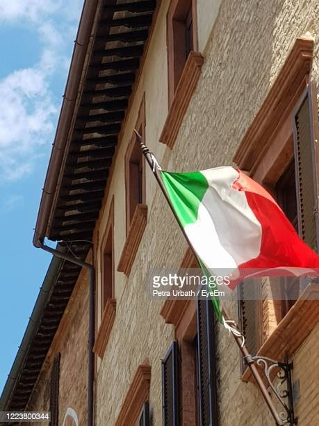 low angle view of italien flag hanging outside building - italien stock pictures, royalty-free photos & images