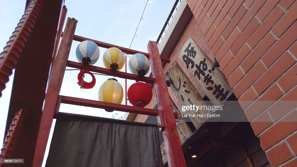 Low Angle View Of Japanese Lanterns Hanging By Brick Wall ...
