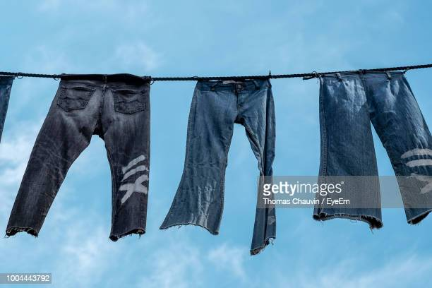 low angle view of jeans drying against sky - パンツ ストックフォトと画像