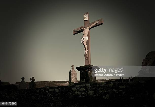 Low Angle View Of Jesus Christ Statue On Cross At Dusk