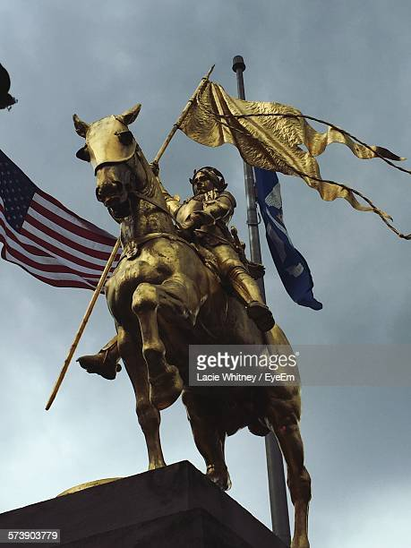 low angle view of joan of arc and american flag against cloudy sky - juana de arco fotografías e imágenes de stock