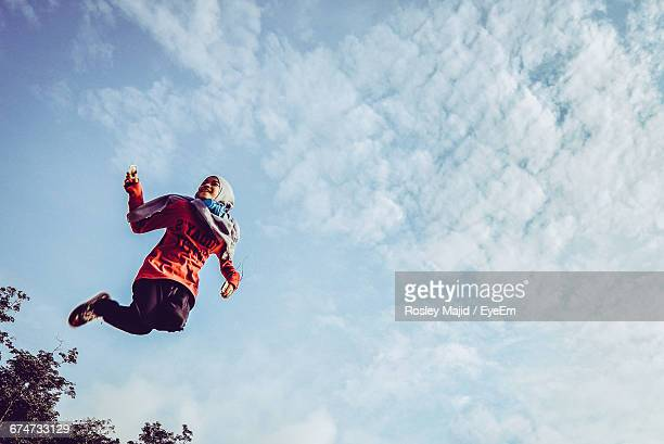 Low Angle View Of Jumping Girl In Headscarf