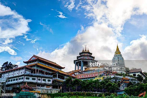 low angle view of kek lok si temple against cloudy blue sky in city - george town penang stock photos and pictures
