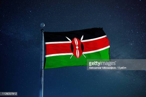 low angle view of kenyan flag against star field sky - kenyan flag stock pictures, royalty-free photos & images