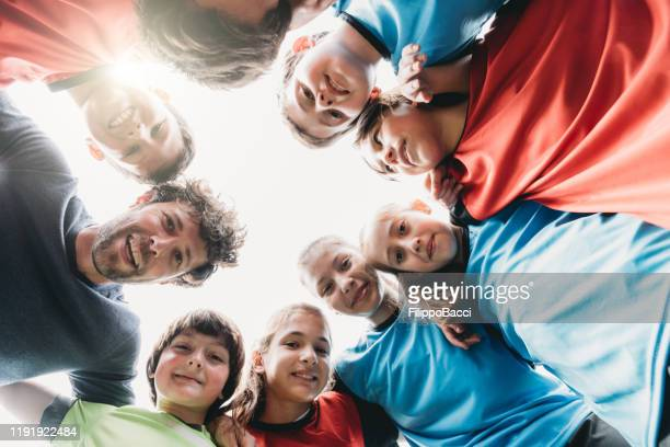 low angle view of kids football school team looking together at camera - junior level stock pictures, royalty-free photos & images