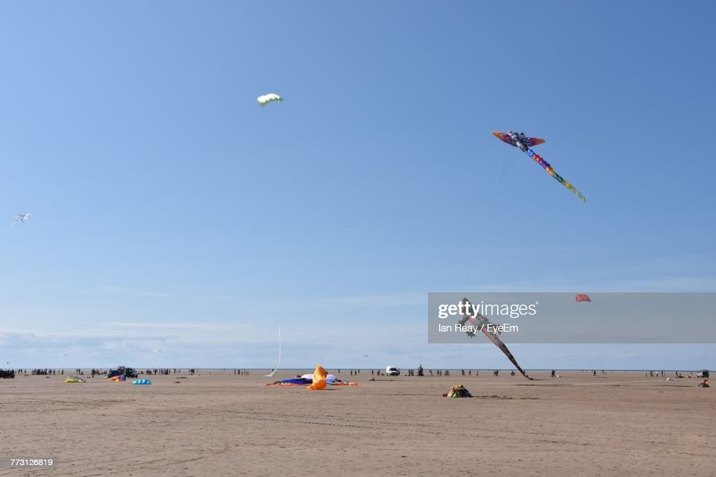 Low Angle View Of Kites Flying Against Blue Sky : Photo
