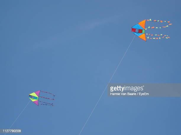 Low Angle View Of Kites Flying In Blue Sky