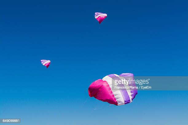 Low Angle View Of Kites Flying In Clear Sky