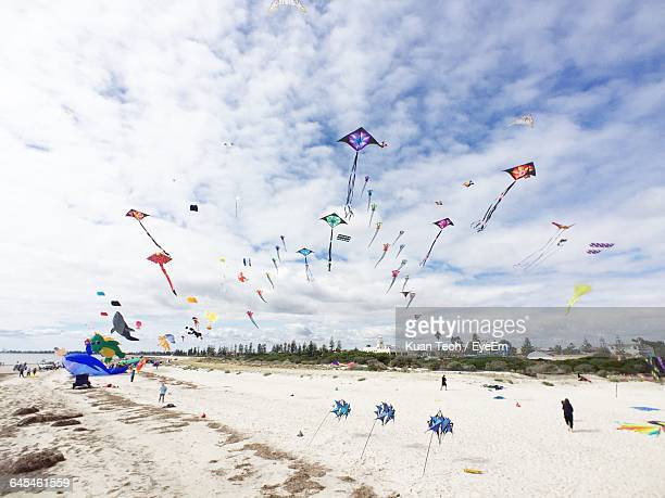 Low Angle View Of Kites Flying Over Beach Against Sky