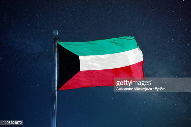 low angle view of kuwaiti flag against star field sky - kuwaiti flag stock pictures, royalty-free photos & images