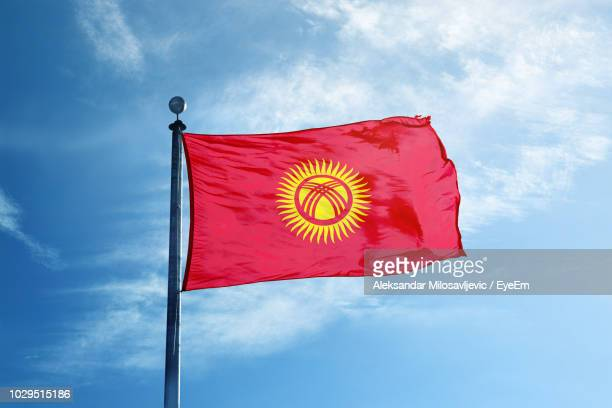 low angle view of kyrgyzstan flag against blue sky - kyrgyzstan stock pictures, royalty-free photos & images