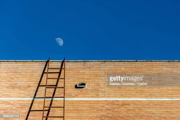 low angle view of ladder on brick wall against clear blue sky - ladder to the moon stock pictures, royalty-free photos & images