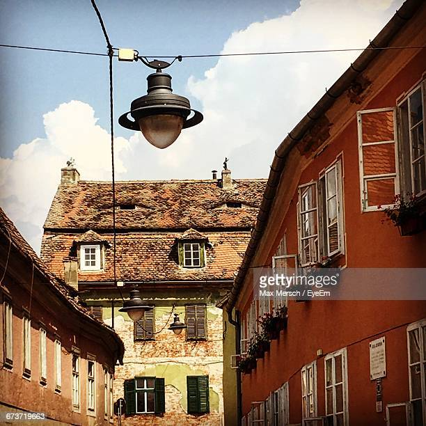 Low Angle View Of Lamp By Buildings Against Sky