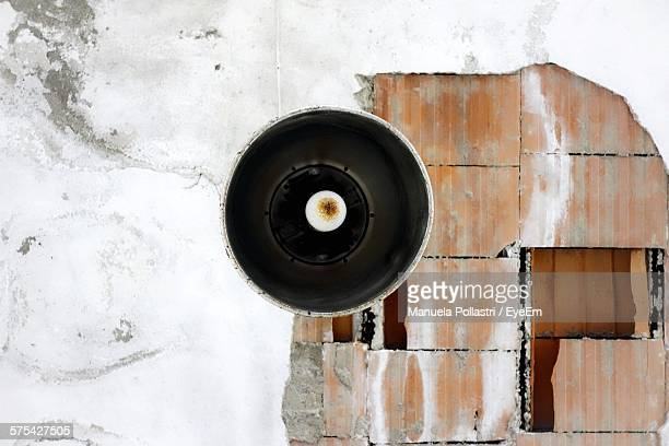 Low Angle View Of Lamp On Broken Ceiling Of Abandoned House