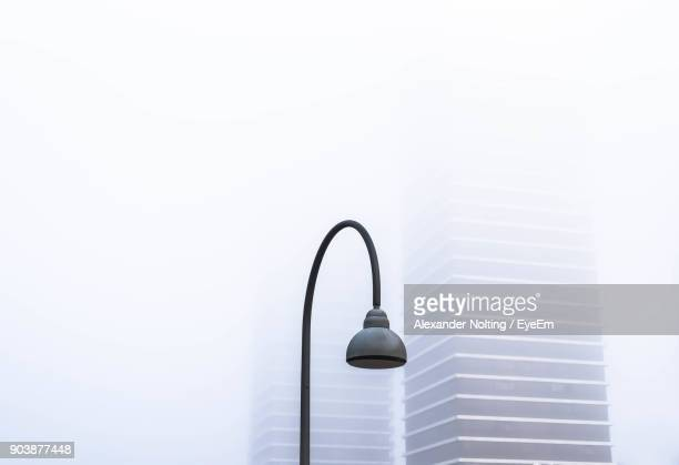Low Angle View Of Lamp Post Against Buildings During Foggy Weather
